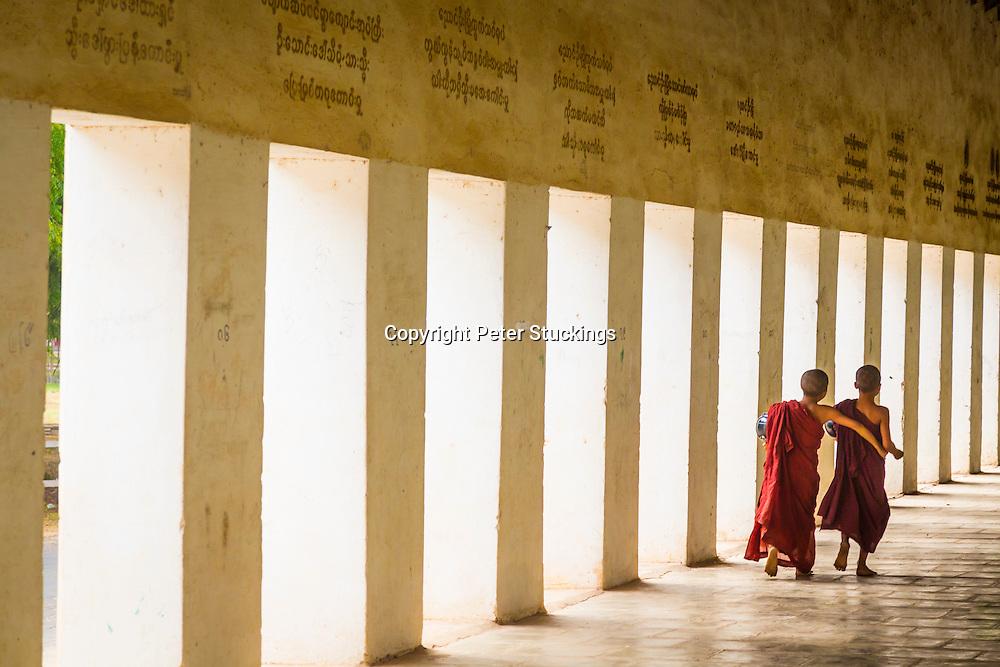Novice monks walk through the corridor at Shwesigon Pagoda, Myanmar