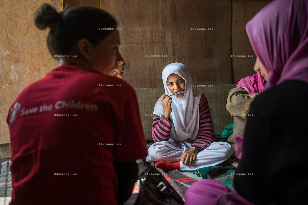 (Alison Griffin to fill in names) (girl's name) and her siblings talk to Save the Children team members about their losses and the devastation for the floods in Abikarpora village on the Dal Lake, Srinagar, Jammu and Kashmir, India, on 25th March 2015. Since the flood, she has been widowed, and is left with four young children and no home. Her family now lives in a temporary shelter built using the emergency shelter kit, and continues their recovery with the help of relief kits such as education kit, food basket, hygiene kit and non-food items from Save the Children. Photo by Suzanne Lee for Save the Children