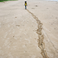 Vijyashree walks along the beach close to the location of her mother's death in the tsunami. <br /><br />Vijitha and Vijyashree Viswanathan, now age 13 and 11, lost their mother and younger brother to the 2004 Asian Tsunami. The sisters continue to live with their father Viswanathan in a small house in the fishing village of Thalanguda, 5km from Cuddalore. The house does not have a toilet and water is supplied for only a short period of the day. Viswanathan married Kayalvizhi just over a year after the tsunami and the couple now have a son Sanjay, born December 2006 and daughter, Monica, born September 2008. <br /><br />Vijitha and Vijyashree continue to be close to their father who admits to feelings of guilt about his re-marriage. Viswanathan shows all of his children more attention than the average father in a patriachal south Indian fishing village. With little opportunity to reminisce for the past, Vijitha and Vijyashree have got on with their lives and appear relatively content. They both rely on each other for support and enjoy the reassuring company of their paternal aunt Shanti who lives in a neighbouring house. Shanti accuses Kayalvizhi of being indifferent to the needs of her adopted daughters and forcing them to undertake too many household chores. Shanti is pursuing the idea of having Vijita and Vijyashree live with their maternal grandmother where she feels their mother's extended family would be more attentive to the girls' needs. On holidays the sisters have the opportunity to visit their maternal grandmother Govindamal who lives in the neighbouring district of Nagapattinam. Both Vijitha and Vijyashree continue to pursue their studies at Thalanguda government school. <br /><br />Photo: Tom Pietrasik<br />Cuddalore, Tamil Nadu, India<br />November 23rd 2008<br /><br />THIS PHOTOGRAPH IS THE COPYRIGHT OF TOM PIETRASIK. THE PHOTOGRAPH MAY NOT BE REPRODUCED IN ANY FORM OTHER THAN THAT FOR WHICH PERMISSION WAS GRANTED. THE PHOTOGRAPH MAY NOT BE MANIPULATE