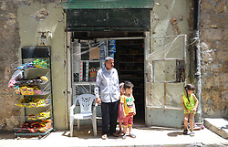 (170729) -- ALEPPO (SYRIA), July 29, 2017 (Xinhua) -- Muhammad Deeb, 65, stands with grandchildren in front of his shop in Ansari neighborhood, east of Aleppo city, northern Syria, July 28, 2017. The rebels had stayed in the east of Aleppo for five years before they evacuated in December of 2016. Seven months after the Syrian army took full control over the city, life starts to beat again through devastation and destruction in the area. (Xinhua/Ammar Safarjalani) (zjy) (Photo by Xinhua/Sipa USA)