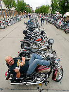 Manfred Richter of Frankfurt, Germany video tapes from the back of his motorcycle at the final Harley-Davidson party in downtown Milwaukee August 31, 2003.  The legendary American motorcycle company celebrated its 100th anniversary over the last four days.  Richter's bike, a Yamaha, had a for sale sign on it.    REUTERS/Rick Wilking