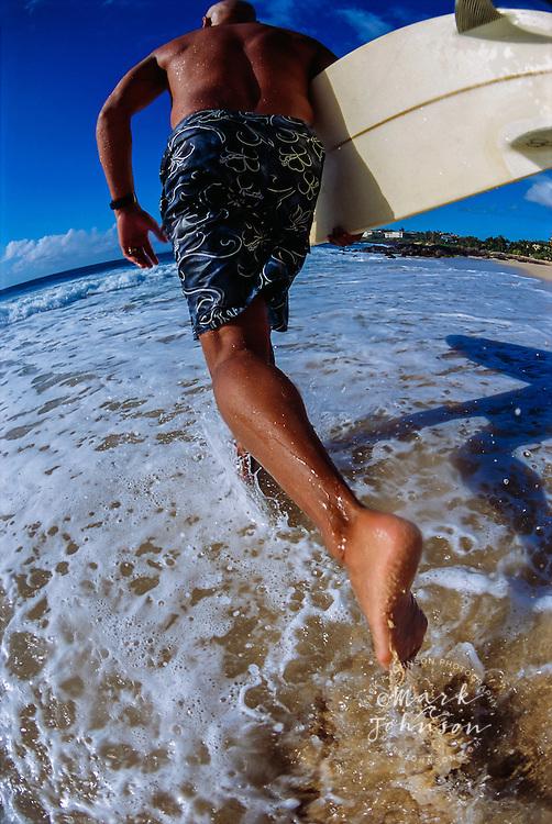 Kauai, Hawaii, USA --- Surfer Heading into Water