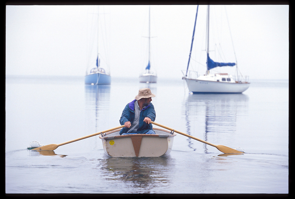 A MAN ROWS A DINGHY TO SAILBOATS ANCHORED IN THE FOG ON LAKE SUPERIOR IN MARQUETTE MICHIGAN.