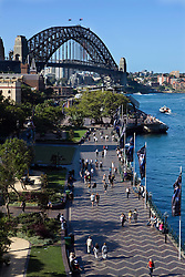 People walk along the Sydney Harbor in The Rocks, with the Sydney Harbor Bridge in the background, Sydney, New South Wales, Australia