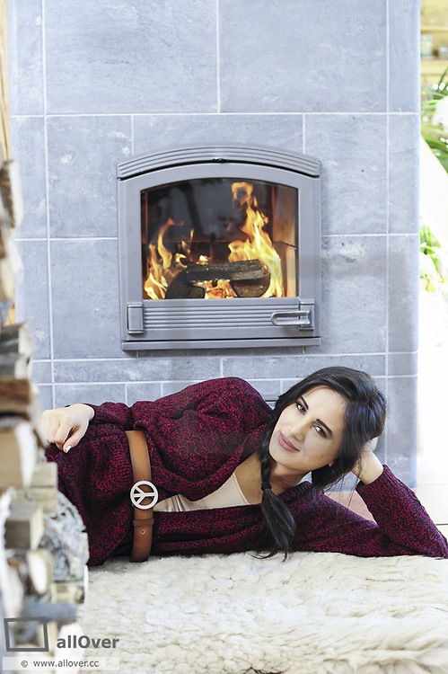 Young, beautiful woman heating in living room (model-released)