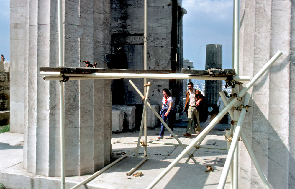 A man and woman walking along the Parthenon platform between columns and bypassing the scaffolding beginning to be erected preparatory to the Acropolis restoration program that began in 1978.