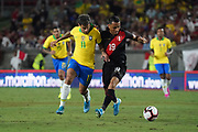 Brazil midfielder Phillippe Coutinho (11) and Peru midfielder Yoshimar Yotun (19) battle for the ball during an international friendly soccer match, Tuesday, Sept. 10, 2019, in Los Angeles. Peru defeated Brazil 1-0.