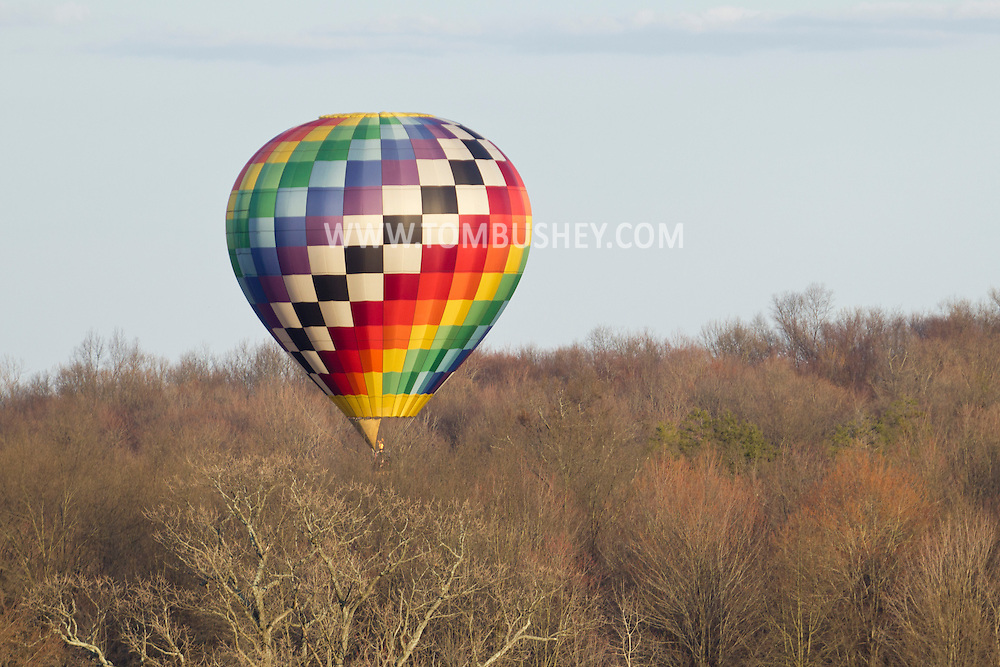 Middletown, New York - A hot air balloon flies over the trees after taking off from Randall Airport on  April 12, 2014.r the trees after taking off from Randall Airport on  April 12, 2014.