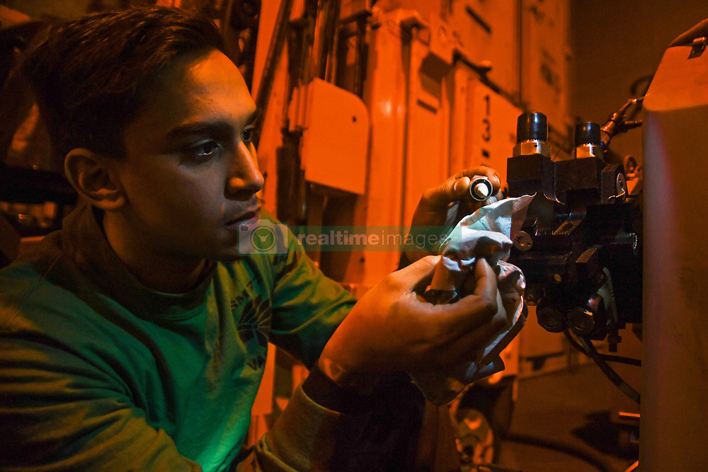 """180924-N-MK318-0053<br /> NORTH ATLANTIC (Sept. 24, 2018) Aviation Electronics Technician 3rd Class Alejandro Vargas, assigned to the """"Proud Warriors"""" of Helicopter Maritime Strike Squadron (HSM) 72, changes oil on helicopter equipment in the hangar bay aboard the Nimitz-class aircraft carrier USS Harry S. Truman (CVN 75). Currently operating in the U.S. 6th Fleet area of operations, Harry S. Truman will continue to foster cooperation with regional allies and partners, strengthen regional stability, and remain vigilant, agile and dynamic. (U.S. Navy photo by Mass Communication Specialist 3rd Class Victoria Granado/Released)"""