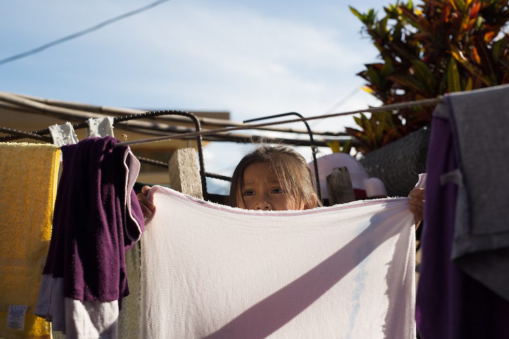 Gladys Perez, 8, helps with chores by hanging recently washing laundry on a clothes line to dry. The Perez family, like many other people living in rural Guatemala, use the lake to wash their laundry and to bathe.
