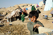 UNHCR returnees at Mohajir Qeshlaq, Sholgara District, Balkh Province, Afghanistan, on Monday, October 6, 2008.  The families face desperate conditions with winter coming, unable to build homes due to unresolved land issues.  Many are making bricks from the earth but are unable to build.   Young men are returning to Pakistan for work, while others are laboring in the cornfields attempting to feed their family...Background:  In early summer 2008, around 150 families returned to Sholgara district from Jalozai camp in Pakistan. They had acquired a piece of land before return, but due to ethnic tension the surrounding communities fiercely opposed the settlement of Pashtuns in their midst. For 4 months they lived in a camp-like situation in Sholgara centre but now the government has identified a piece of land for them in Mohajir Qeshlaq. This year UNHCR was unable to include them in its shelter program due to the unsettled land issue, but they are expected to be included in the 2009 shelter program.  .