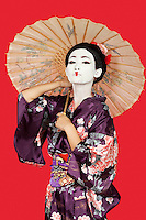 Portrait of Japanese woman in kimono holding parasol against red background