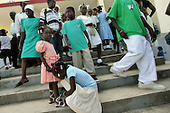 A girl helps her friend with her shoes after they and fello parishoners attend Sunday mass at the Saint Roch Catholic church atop the Saint Roch mountain above Carrefour, Haiti.