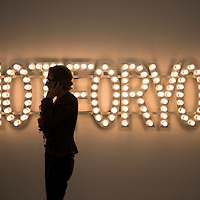 London, UK - 15 October 2014: a woman speaks on the phone and walks past a neon reading ' Not For You' during the first day of Frieze Art Fair and Frieze Masters in Regent's Park.