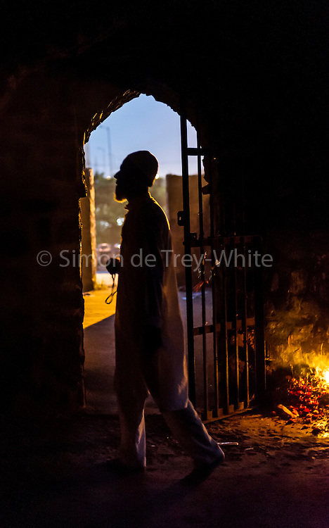 20th August 2015, New Delhi, India.  A  Muslim man holding prayer beads paces in the ruins of Feroz Shah Kotla in New Delhi, India on the 20th August  2015<br /> <br /> PHOTOGRAPH BY AND COPYRIGHT OF SIMON DE TREY-WHITE a photographer in delhi<br /> + 91 98103 99809. Email: simon@simondetreywhite.com<br /> <br /> People have been coming to Firoz Shah Kotla to pray to and leave written notes and offerings for Djinns in the hopes of getting wishes granted since the late 1970's. Jinn, jann or djinn are supernatural creatures in Islamic mythology as well as pre-Islamic Arabian mythology. They are mentioned frequently in the Quran  and other Islamic texts and inhabit an unseen world called Djinnestan. In Islamic theology jinn are said to be creatures with free will, made from smokeless fire by Allah as humans were made of clay, among other things. According to the Quran, jinn have free will, and Iblīs abused this freedom in front of Allah by refusing to bow to Adam when Allah ordered angels and jinn to do so. For disobeying Allah, Iblīs was expelled from Paradise and called &quot;Shayṭān&quot; (Satan).They are usually invisible to humans, but humans do appear clearly to jinn, as they can possess them. Like humans, jinn will also be judged on the Day of Judgment and will be sent to Paradise or Hell according to their deeds. Feroz Shah Tughlaq (r. 1351&ndash;88), the Sultan of Delhi, established the fortified city of Ferozabad in 1354, as the new capital of the Delhi Sultanate, and included in it the site of the present Feroz Shah Kotla. Kotla literally means fortress or citadel.