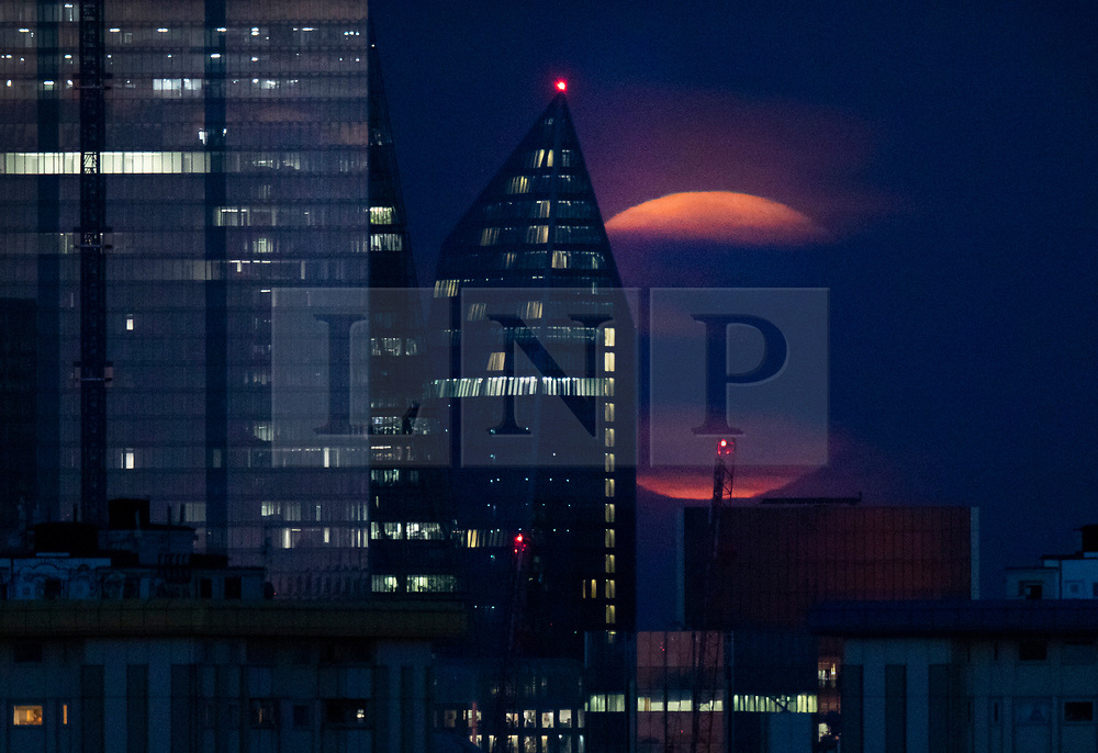 © Licensed to London News Pictures. 15/08/2019. London, UK. The Sturgeon full moon rises over the London skyline. The August full moon is known as the Sturgeon Moon because native American indians believed that the sturgeon fish could most easily be caught at that time. Photo credit: Peter Macdiarmid/LNP