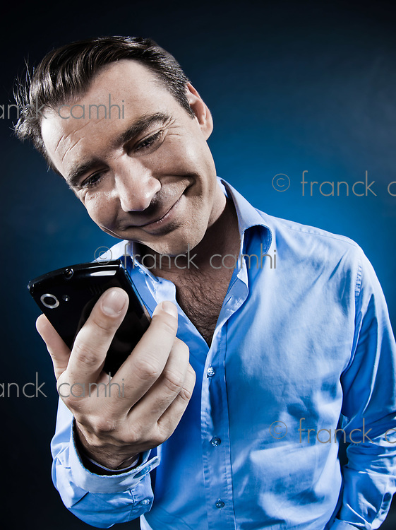 caucasian man smiling happy with cellphone portrait isolated studio on black background