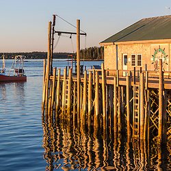 The dock and processing building at Moosabec Mussels in Jonesport, Maine. Owner Ralph Smith's mussel harvesting boat is in the distance.
