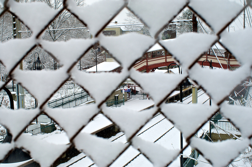 Snow is stuck on a fence, behind it lays Allens Lane train station on SEPTA's Chestnut Hill West line.