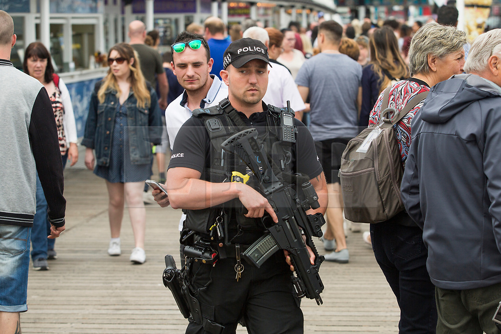 © Licensed to London News Pictures. 28/05/2017. Brighton, UK. Armed officers of the Brighton and Hove police force patrol the Brighton Palace Pier. Police have increased the number of armed officers on the street in the aftermath of the Manchester Bombing. Photo credit: Hugo Michiels/LNP
