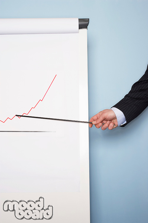 Businessman pointing at graph on easel close-up of hand