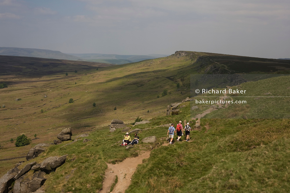 Walkers on Long Causeway, at Stanage Edge gritstone cliffs, Peak District National Park, Derbyshire..Located in the Peak District National Park in England Stanage Edge is the largest of the gritstone edges that overlook Hathersage in Derbyshire. Stanage Edge at approximately 4 miles in length and 458m at its highest point is the largest of the gritstone cliffs that overlook Hathersage, Derbyshire. The area is one of the most popular locations in the Peak District National Park for climbing and walking with hundreds of rock climbing routes to challenge all ranges of ability. Walkers are drawn to the area to enjoy the varied moorland scenery with stunning views across the surrounding countryside including Hathersage, Castleton and the 'Shivering Mountain', Mam Tor in the west. A walk along the edge is an easy route but the exposed cliff can make conditions difficult throughout the year as it is often battered by wind, rain and regular snowfall in the winter months. There are a number of popular walks including routes along the remains of a Roman Road and towards Redmires Reservoir to the east as well as longer walks such as those including the nearby Longshaw Estate. Sopurce http://www.stanageedge.co.uk