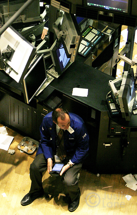 A trader sits on the floor of the New York Stock Exchange at the end of trading in New York, New York on Tuesday 27 February 2007. The Dow Jones Industrial average ended down 416 points, about 3 percent, after China's equity market tumbled today.