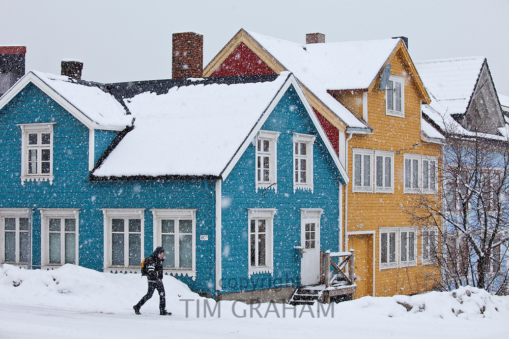 Man walks past traditional wooden buildings along Storgata in the quaint area of Tromso, in the Arctic Circle in Northern Norway