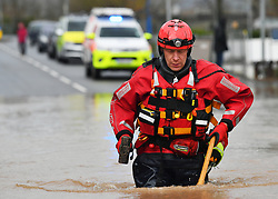 A member of the Mountain Rescue team holding a hammer as he attempts to rescue a man from a house that is surrounded by heavy flood water in Monmouth, in the aftermath of Storm Dennis.