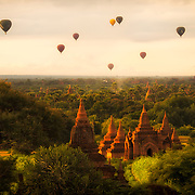 BAGAN, Myanmar (Burma) - Hot air balloons rise in the still morning air in tourism flights over the pagodas of the Bagan Archaeological Zone in Myanmar (Burma). Bagan was the ancient capital of the Kingdom of Pagan. During its height, from the 9th to the 13th century, over 10,000 Buddhist temples and pagodas were built. Several thousand of them survive today.