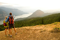 A young couple enjoys the view of the Columbia River Gorge from the Dog Mountain Trail, Washington.