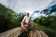 29 JUNE 2013 - BATTAMBANG, CAMBODIA:  A man drives a Bamboo Train from the terminal station near Battambang to O Sra Lav, a small village 7kms southeast of Battambang. The bamboo train, called a norry (nori) in Khmer is a 3m-long wood frame, covered lengthwise with slats made of ultra-light bamboo, that rests on two barbell-like bogies, the aft one connected by fan belts to a 6HP gasoline engine. The train runs on tracks originally laid by the French when Cambodia was a French colony. Years of war and neglect have made the tracks unsafe for regular trains.  Cambodians put 10 or 15 people on each one or up to three tonnes of rice and supplies. They cruise at about 15km/h. The Bamboo Train is very popular with tourists and now most of the trains around Battambang will only take tourists, who will pay a lot more than Cambodians can, to ride the train.       PHOTO BY JACK KURTZ