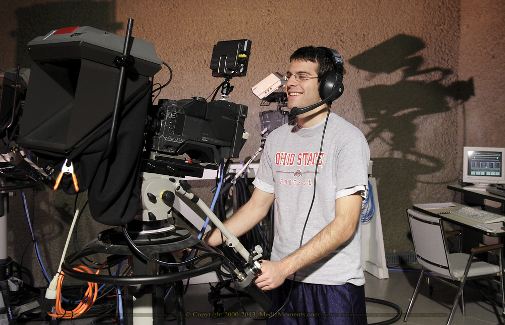 "Garrett Senney, has been a volunteer with the Miami Valley Communications Council for five years.  Here he demonstrates one of the things he does as a volunteer: run camera in ""Studio A.""  He also knows how to use the computer system behind him to operate the lights in the studio."