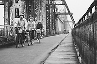 Men ride their bicycles across Long Bien Bridge in northern Vietnam.