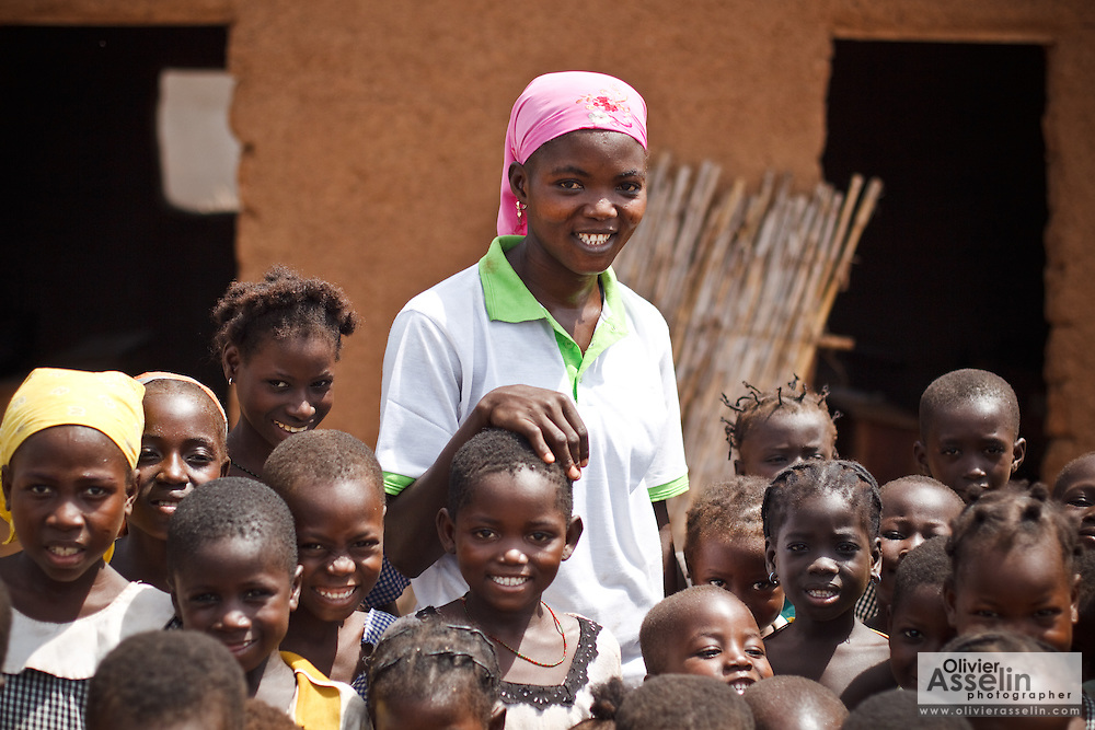 Abdulai Sadia stands with children she and other volunteers teach in the community of Kunayili, near Gushegu, Northern Ghana, on Wednesday November 2, 2011.