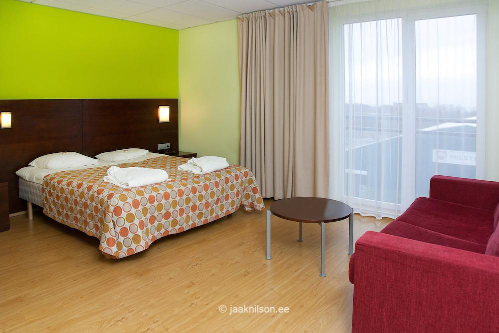 Bedroom with modern furniture and large sofa in Viimsi Spa Hotel in Tallinn, Estonia