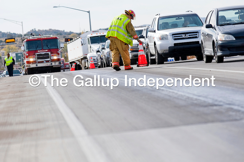 110212       Cable Hoover<br /> <br /> Gallup firefighter Wes Bowers sets up cones to block on northbound lane of the Munoz over pass in Gallup Friday. A passing tractor-trailer leaked a large quantity of anti-freeze that left the road slick and treacherous for other traffic.