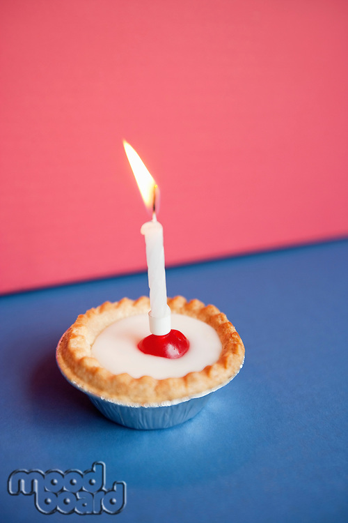Close-up of candle burning on cupcake over colored background