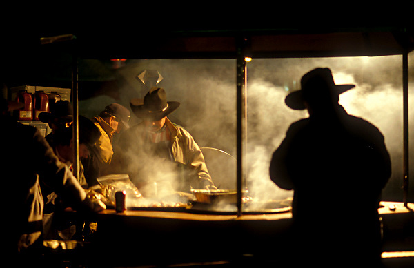Group of cowboys cooking at an indoor kitchen