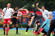 Hugo Inglis of New Zealand goes flying after a clash with the Engalnd keeper during the bronze medal match between New Zealand and England. Glasgow 2014 Commonwealth Games. Hockey, Bronze Medal Match, Black Sticks Men v England, Glasgow Green Hockey Centre, Glasgow, Scotland. Sunday 3 August 2014. Photo: Anthony Au-Yeung / photosport.co.nz