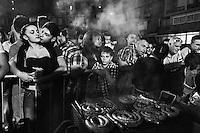 Residents of Librino, a working-class district and mafia stronghold in the outskirts of Catania, Sicily, wait their turn for a free portion of sausage during the campaign closing party for Mayor Raffaele Stancanelli, the center-right candidate running for re-election, on June 7th 2013.<br /> <br /> ###<br /> <br /> Catania, giugno 2013. I residenti del quartiere Librino aspettano il loro turno per il panino con salsiccia offerto dal sindaco uscente Raffaele Stancanelli durante la festa di chiusura della sua campagna elettorale per le elezioni amministrative. Per l'occasione sono stati acquistati 500kg di salsiccia e 500kg di carne di cavallo.
