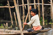 A young girl gets around by rowing her longtail boat on Inlé Lake, Burma (Myanmar)