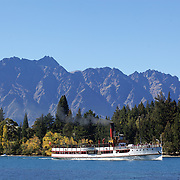 The TSS Earnslaw,  a 1912 Edwardian vintage twin screw steamer on the waters of Lake Wakatipu  with The Remarkables mountain range forming a backdrop in Queenstown, New Zealand. .It is one of the oldest tourist attractions in Central Otago, and the only remaining passenger-carrying coal-fired steamship in the southern hemisphere..The TSS Earnslaw heads along Lake Wakatipu from Queenstown  daily, running tourist trips to Walter Peak Station passing magnificent  peaks and contrasting shoreline foliage along the lakeside. Queenstown, New Zealand. 30th March 2011. Photo Tim Clayton
