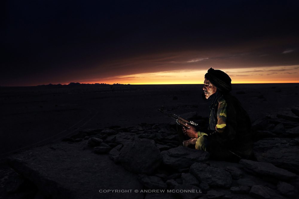 Malainin Aomar, 66, soldier of the Polisario Front, pictured watching the Moroccan wall near Auserd, in Polisario controlled Western Sahara (Saharawi Arab Democratic Republic)...I was born in Auserd in 1953. Since I was a little boy I studied the Koran and I learnt the difference between good and bad. I was taught by a Spanish soldier for a few years who my father hired. My father was a soldier in the Spanish army and we moved a lot. In August 1974 I joined the Polisario Front. I joined because they were an organisation fighting for the liberation of Western Sahara which had been occupied by the Spanish for almost 100 years. I believed in the Polisario's ideals. ..In September 1975 Spain began to leave all their bases and release the Saharawi soldiers. Polisario knew something was happening and began to prepare for a new kind of conflict. We never trusted Spain. There was a big meeting between all the countries and Algeria and Libya supported independence for Western Sahara, but something went wrong. Then we knew on 14th November 1975 Spain signed the Triple Agreement with Morocco and Mauritania to divide up our land. ..These days when I am watching the wall and I see the city of my birth on the other side it really injures me. Auserd is important to me and to be here and not be able to do anything is terribly hard. Sometimes it makes me cry. I am sixty six years old, for me the future is different than for a young boy. For me the only future is the liberation of my country and my people. If we don't have independence there is no future, all is dark. We have to go back to war, we don't like war but we have to finish this situation, we have been waiting for 34 years, it's enough.