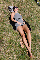 © Licensed to London News Pictures. 12/08/2016. LONDON, UK.  Tia sunbathes and enjoys  the hot and sunny weather today in Green Park in London this lunchtime.  Photo credit: Vickie Flores/LNP