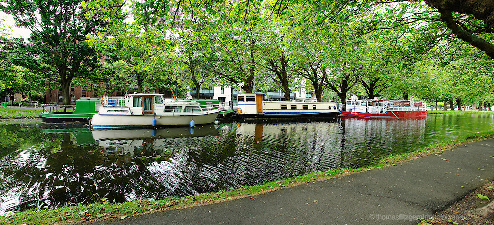 Dublin, Ireland: A group of barges are moored on the Grand Canal on a summers day, at Mespil Road in Dublin City Centre in Dublin, Ireland.