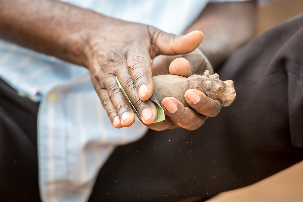 Hands of Zambian man as he sands and shapes hippopotamus figurine with piece of sand paper, Mukuni Village, Zambia