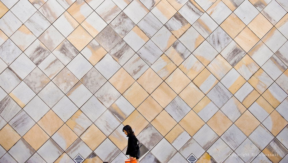 Woman walks past patterned wall of Kumamoto Prefectural Museum of Art, Chibajo branch,  Kumamoto city, Kumamoto Prefecture, Japan