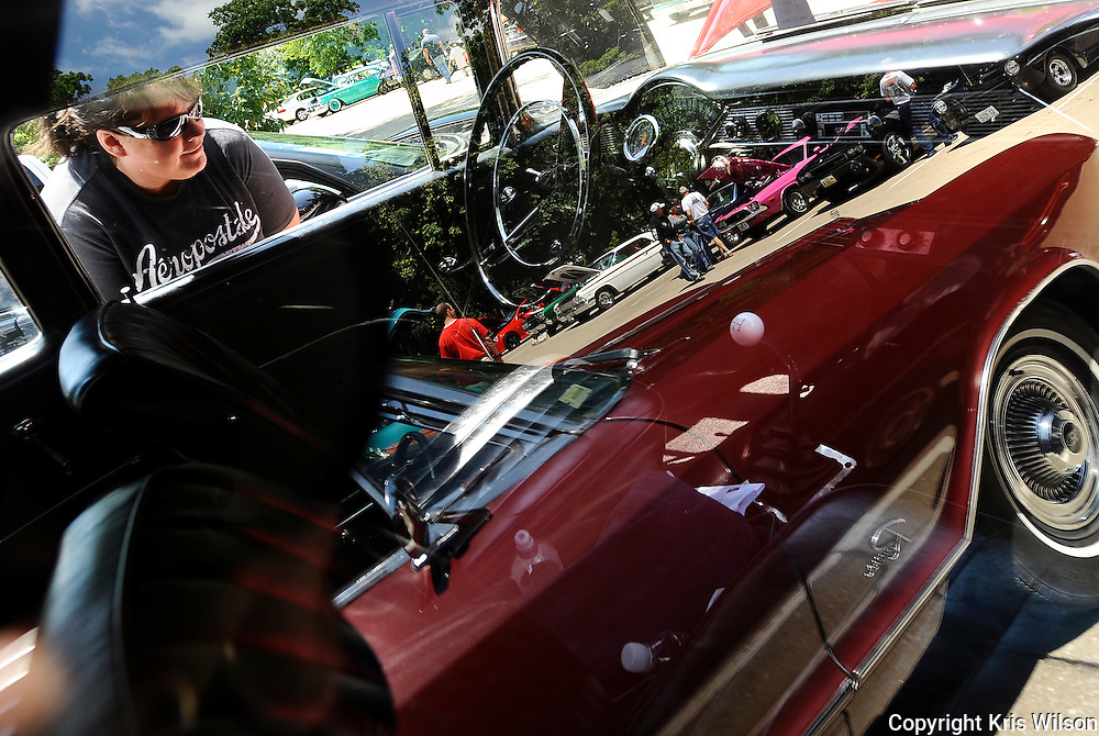 Kris Wilson/News Tribune<br /> Kelly Mutch of Warsaw takes a peek at the interior of a '56 Chevy while several other car enthusiasts are reflected in the passenger window as they check out some the other classic American muscle on display at Memorial Park during the car show portion following the conclusion of the MFA Oil Poker Run.