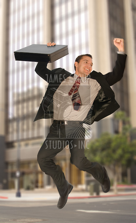 Happy businessman jumping in the middle of an urban street
